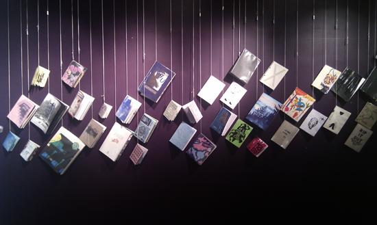 Des dizaines de fanzines sont suspendus par des ficelles dans leur coin supérieur gauche, le long d'un mur pourpre, éclairés par des spots lumineux directionnels